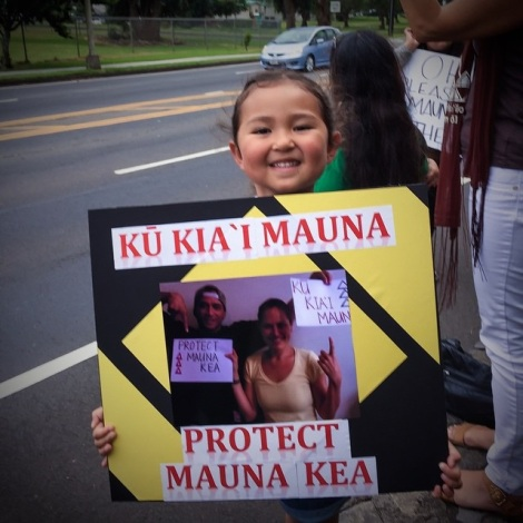 My niece, ʻĀkōlea, sign-waving for Mauna Kea and bringing me along with her.
