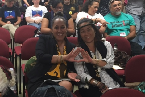 "Mehana Kihoe (left) and protector Leinaala Sleightholm (right) take time to show encouragement with the hand signal synonymous with the world wide ""Kū Kia'i Mauna,"" Protector movement."